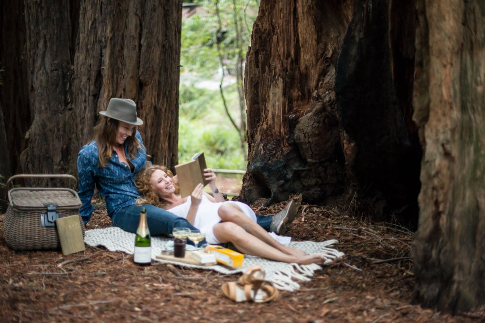 same sex couple smiling and reading good in Old Mill Park Mill Valley at their engagement session