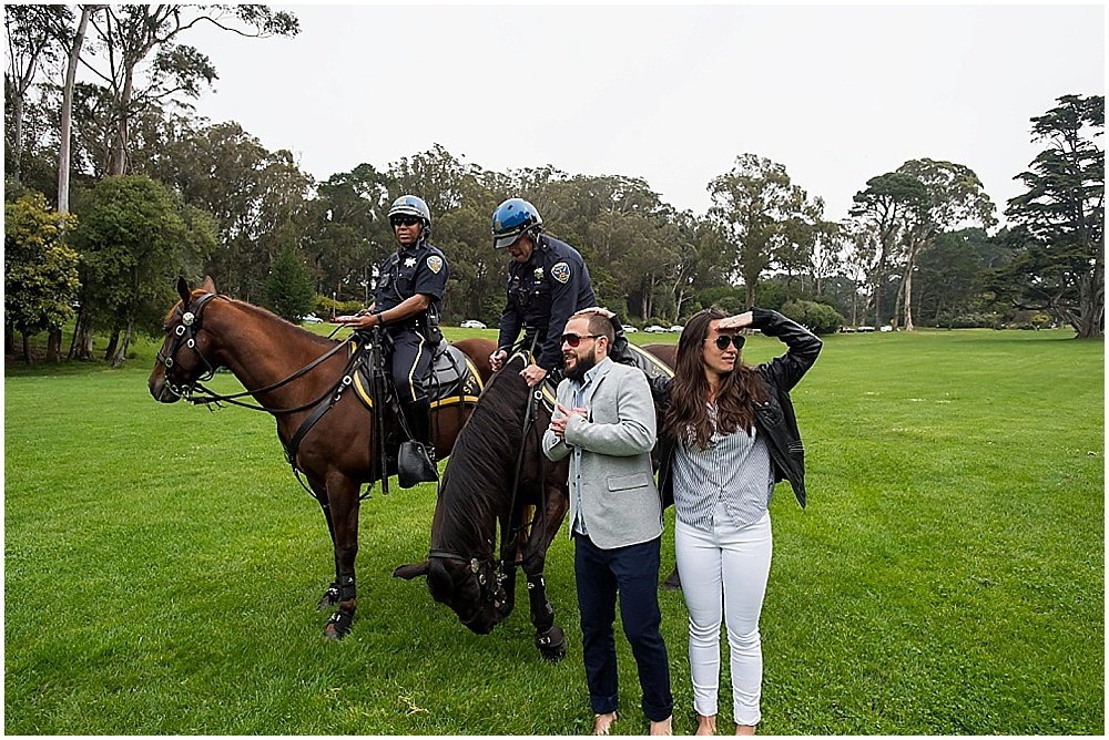 Bride and groom in casual clothes hanging with mounted police in the presidio san francisco