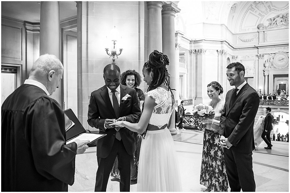 Groom puts ring on bride at San Francisco City Hall Small Wedding black wedding photographer in san Francisco