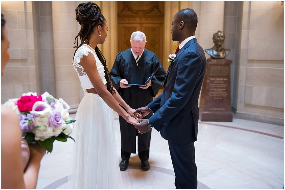 Bride and groom face each-other at at San Francisco City Hall Small Wedding black wedding photographer in san Francisco