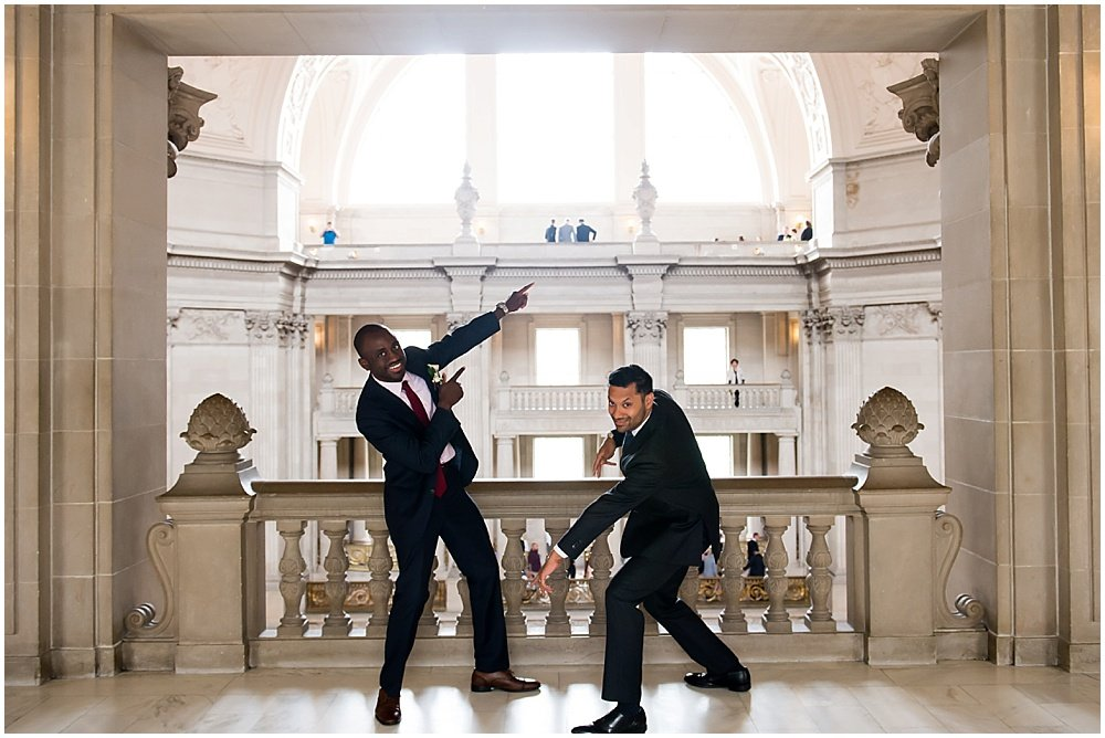 Groom and best man pose pointing in totally different directions at San Francisco City Hall Small Wedding
