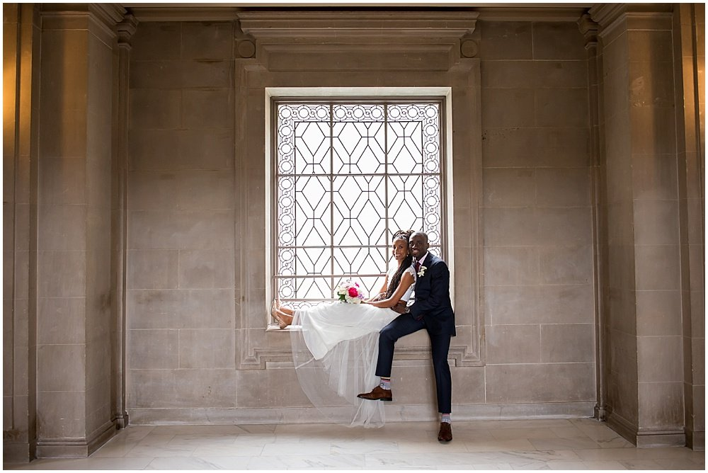 Back together bride and groom sit in windowsill at San Francisco City Hall Small Wedding black wedding photographer in san Francisco