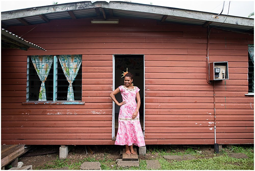 Bride stands in front of house before traditional fijian wedding by chloe jackman photography