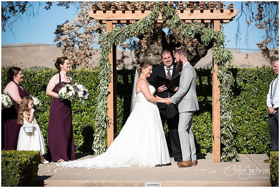 bride and groom laughing at the altar at their outdoor Garre Winery Wedding in Livermore