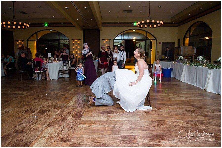 groom grabbing garter belt from bride