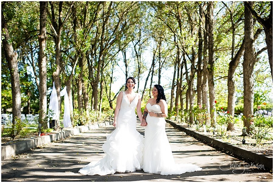 same sex wedding brides on walkway with trees