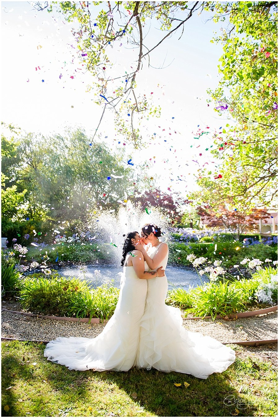 Brides embracing with confetti