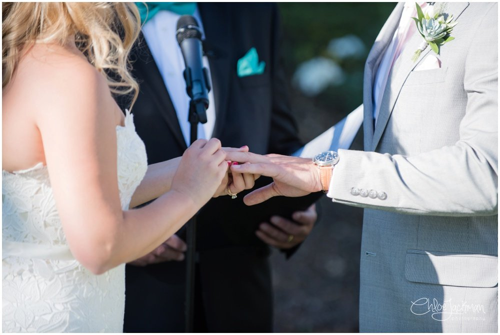 bride putting ring on groom