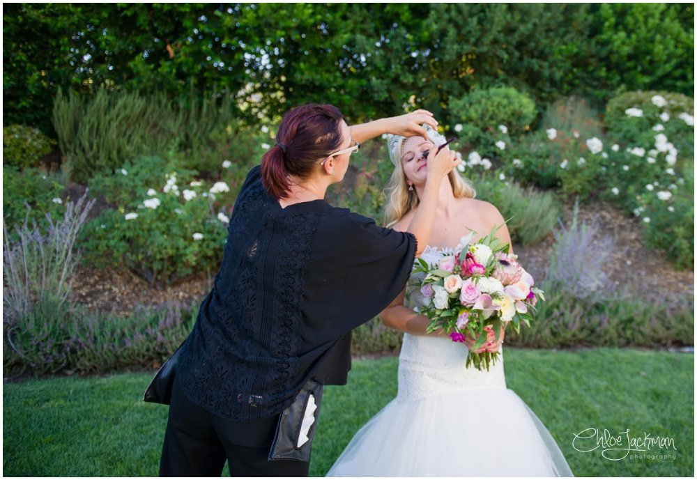 bride getting touch up makeup done by Carrie Aldous Makeup + Hair