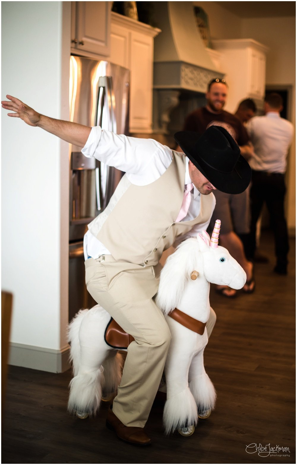 groom riding unicorn in cowboy hat