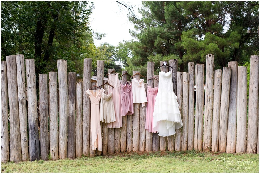 wedding dress and bridemaids dresses hanging on fence at fulford barn wedding in texas