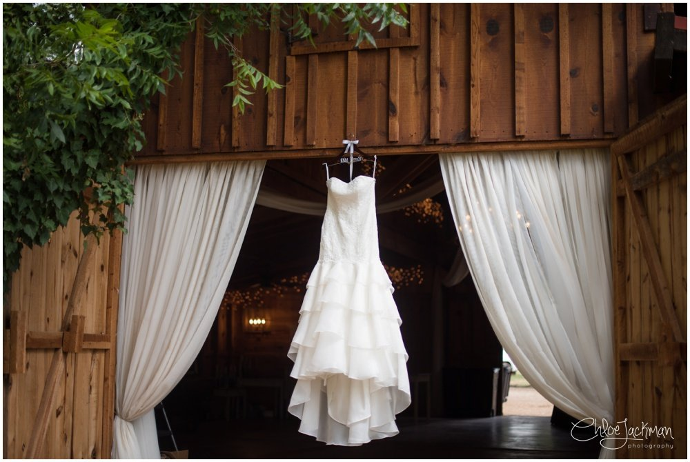 wedding dress hanging on barn at fulford barn wedding in texas