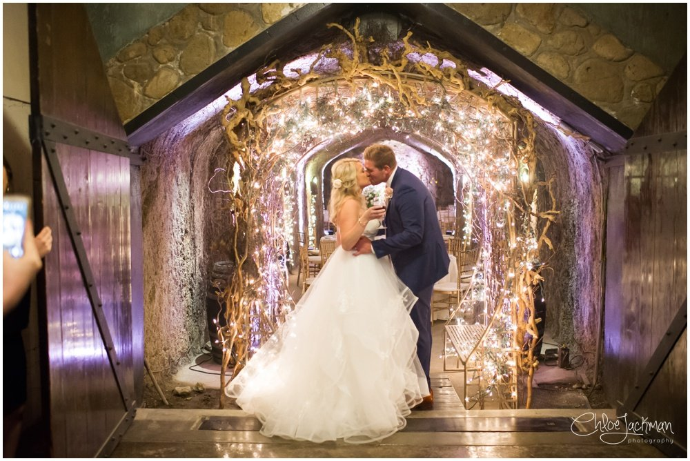 bride and groom kissing under lit altar with lighting by michael's music