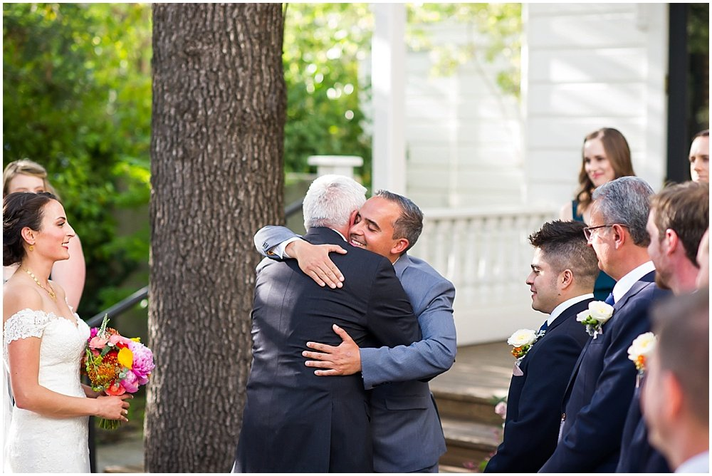 Groom and father of bride hug it out at General's Daughter Wedding by Chloe Jackman Photography