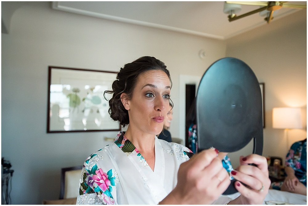 Bride looks at makeup in preparation for reception at the commissary wedding in san francisco