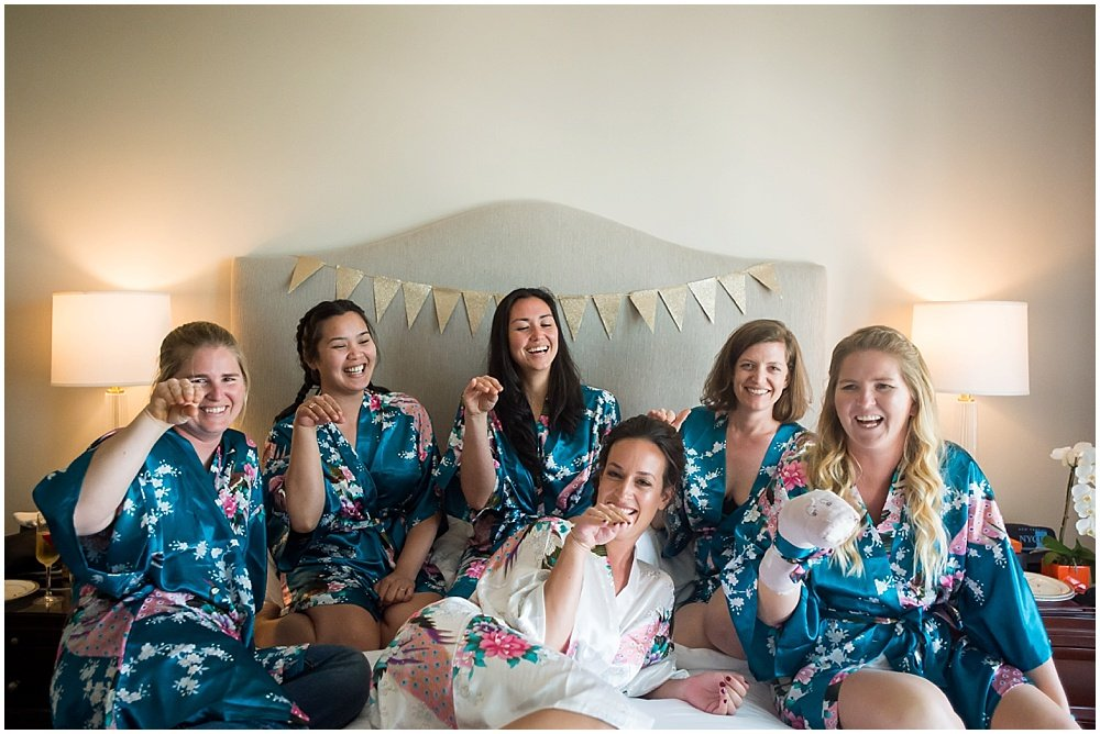 Bride and bridesmaids all pose on bed before going to reception at the commissary wedding in san francisco