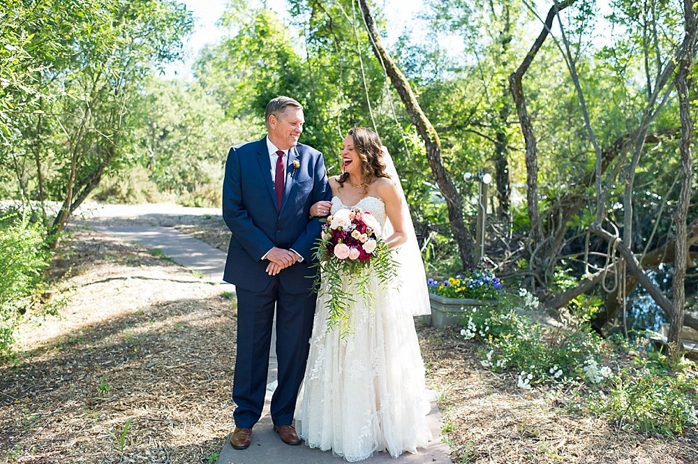 Bride laughing with father of the bride walking to the aisle of hans fahden winery wedding
