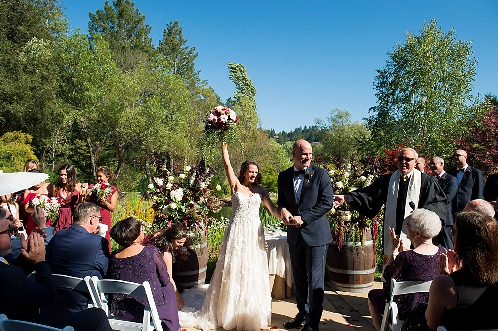 Bride and groom smile and raise bridal bouquet at the end of the ceremony at hans fahden winery wedding