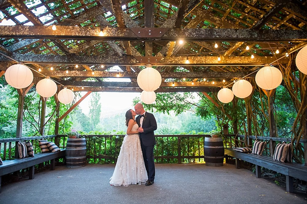 Bride and groom kiss under twinkling lights at hans fahden winery wedding by chloe jackman photography