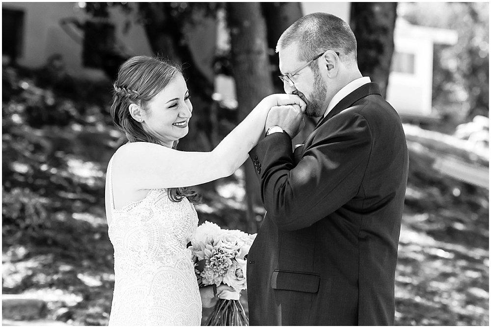 groom kisses brides hand at midsummer Sebastopol wedding by chloe jackman photography