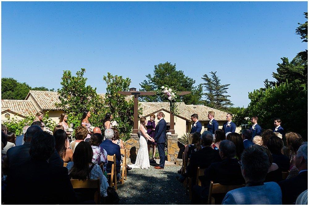 bride and groom at alter at midsummer Sebastopol wedding by chloe jackman photography