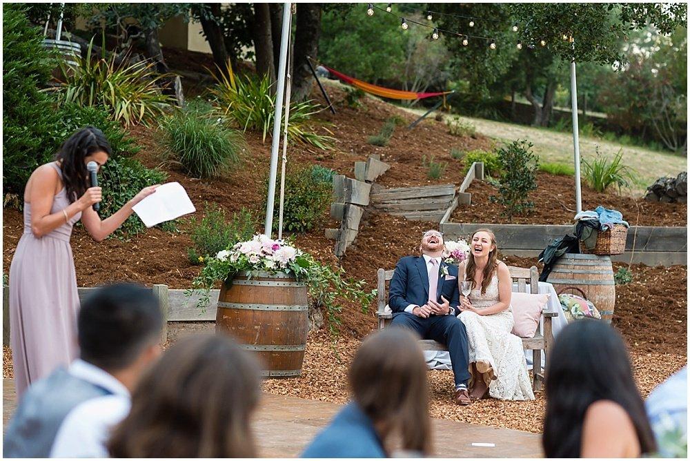 bride and groom laugh at speeches at midsummer sebastopol wedding by chloe jackman photography