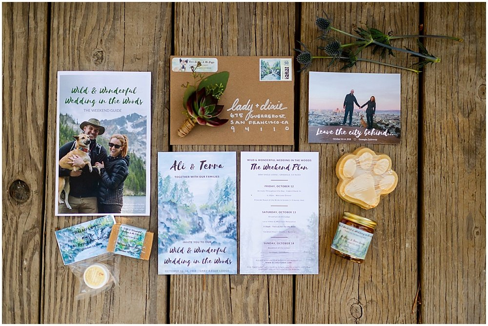 wedding invitations and guest gifts flat lay for gray eagle lodge wedding