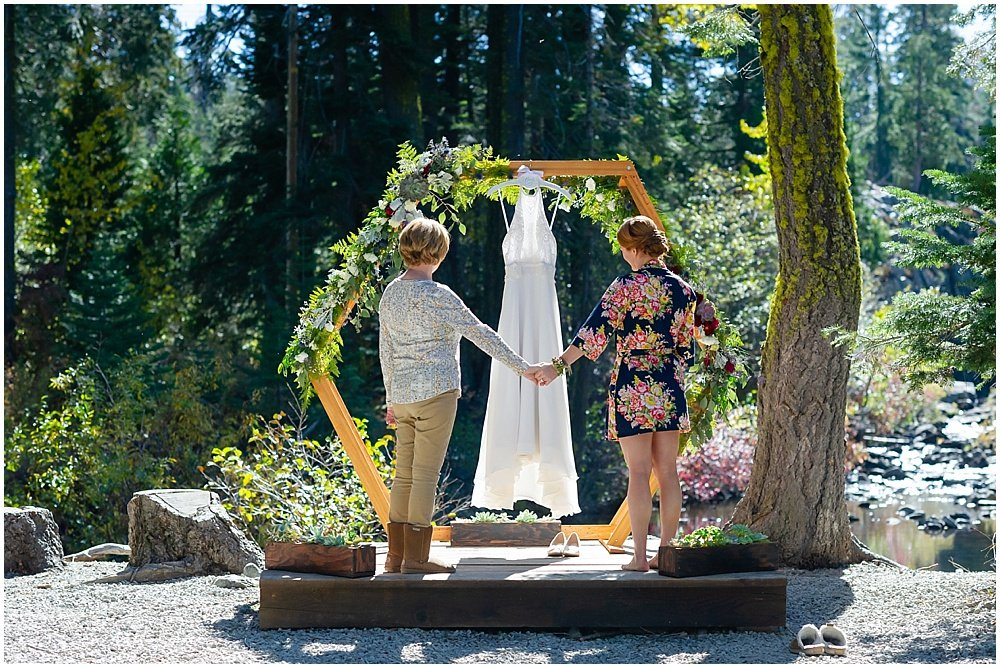 Bride and mom admire the wedding dress for gray eagle lodge wedding