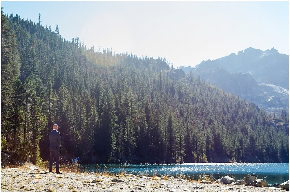 Groom waits for first look by lake at gray eagle lodge wedding by chloe jackman photography