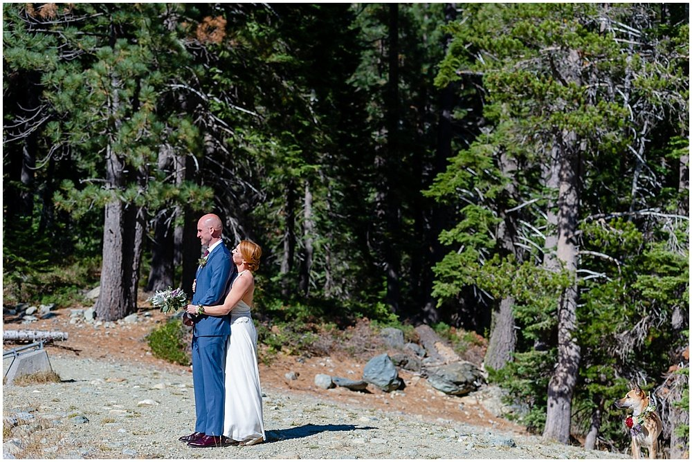 bride hugs groom from behind at gray eagle lodge wedding