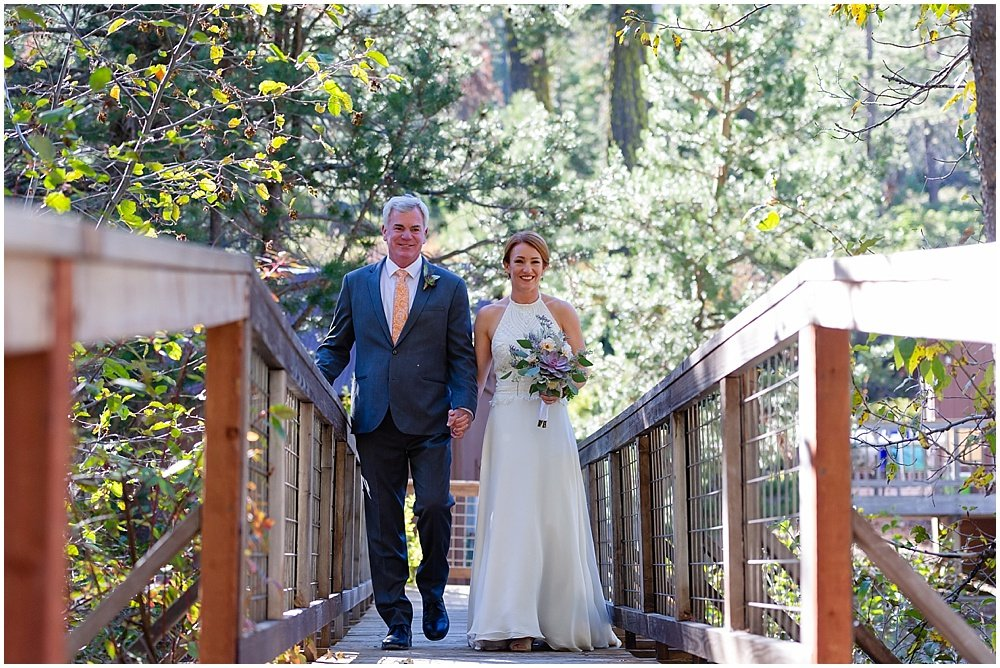 bride walks down aisl at eagle lodge wedding by chloe jackman photography