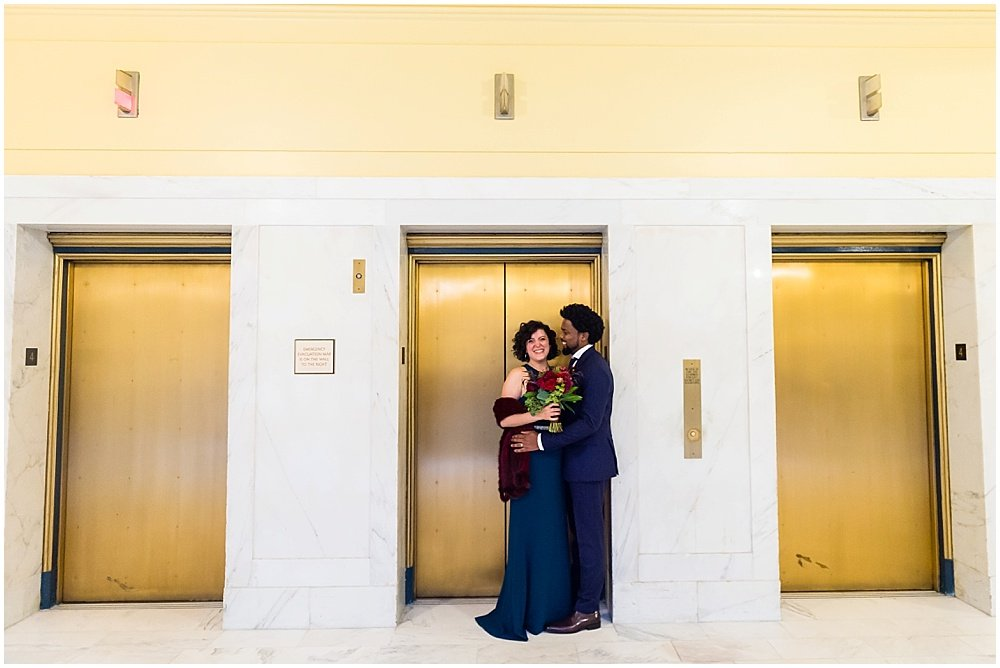 aaron and amanda pose infront of gold elevators at San Francisco City Hall Wedding by chloe jackman photography