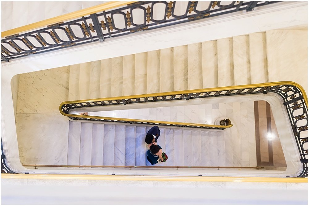 couple walks down stairs at San Francisco City Hall Wedding by chloe jackman photogrpahy