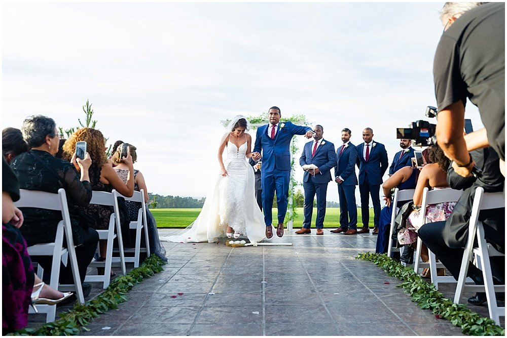 bride and groom jump over broom at tehama golf club wedding by chloe jackman photography