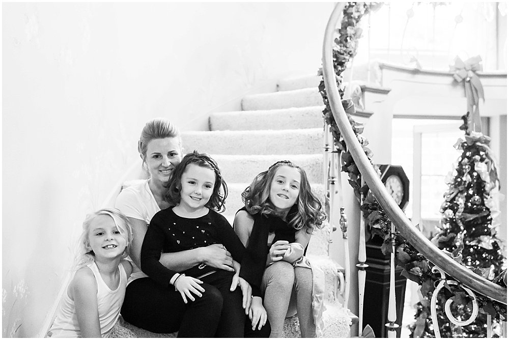 Bride and daughters pose on staircase before wedding