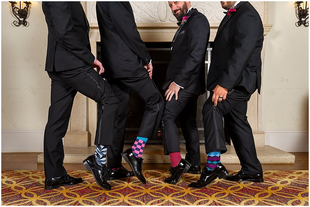 groomsmen show off colorful socks before wedding