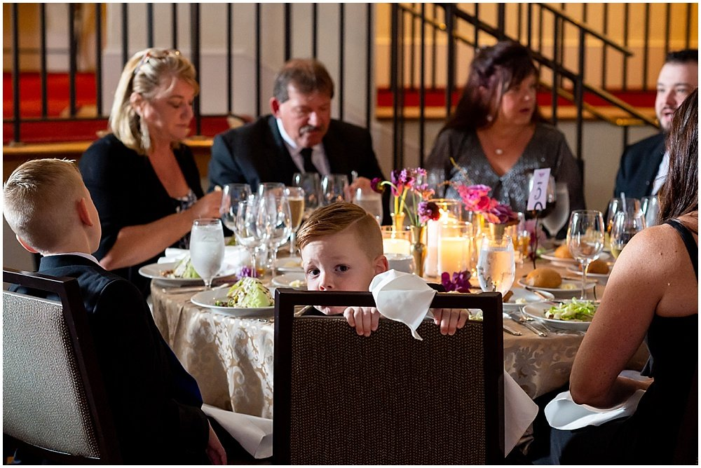 Kids peak over at camera during dinner at Olympic Club Wedding by chloe jackman photography
