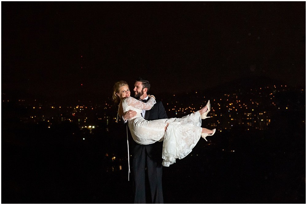 Groom holds bride in front of SF city lights by chloe jackman photography