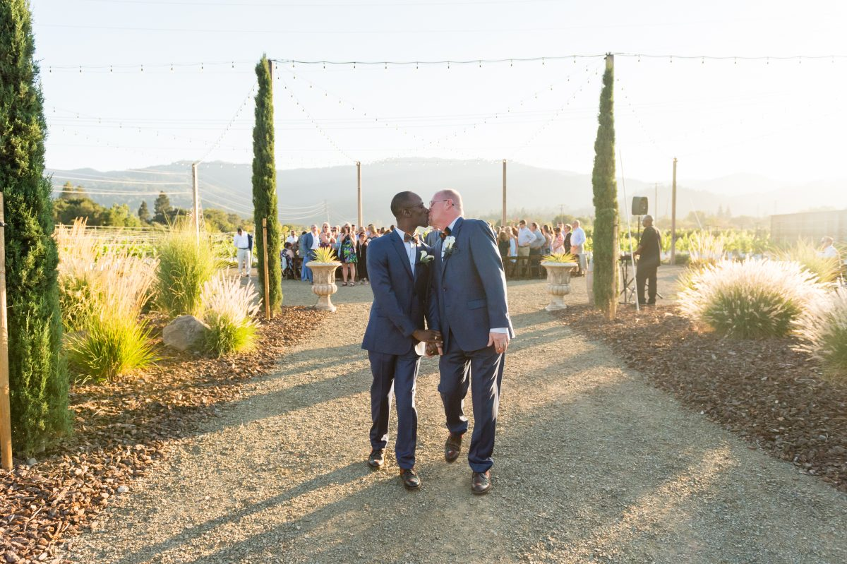 Grooms kiss leaving tre posti wedding ceremony by chloe jackman photography