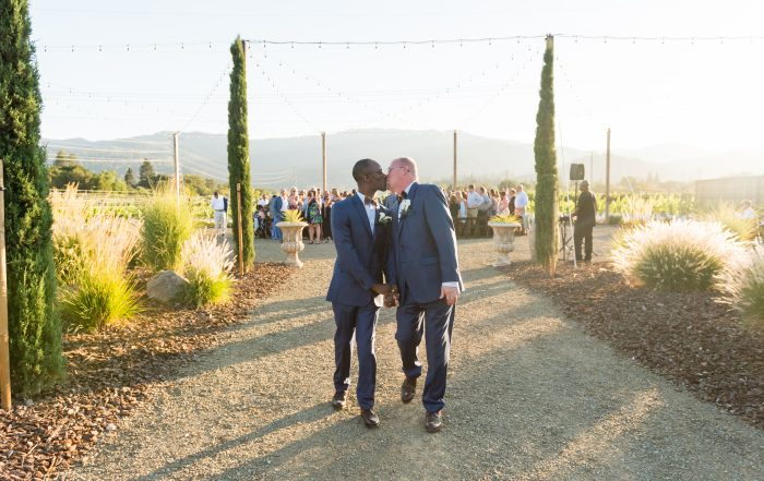 Grooms kiss leaving tre posti wedding ceremony by chloe jackman photography