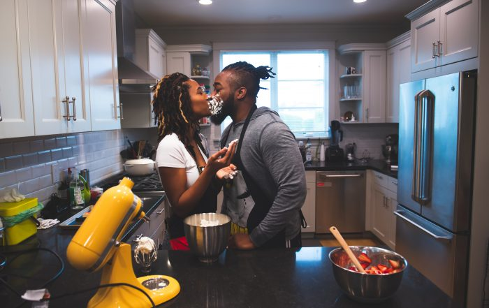 Photos taken before postponing a wedding during a pandemic. Couple in kitchen kissing by chloe jackman photography