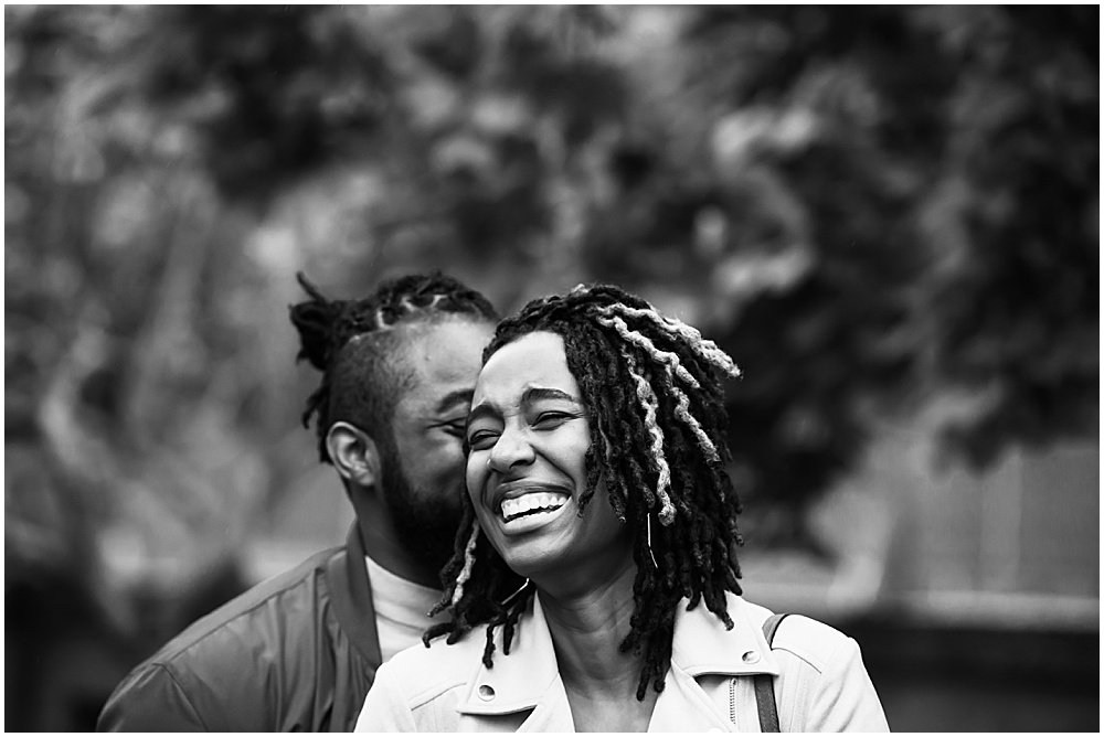 Luther kisses Bria and she laughs. Engagement photo taken before postponing a wedding during a pandemic. Black and white photo of engaged couple by chloe jackman photography