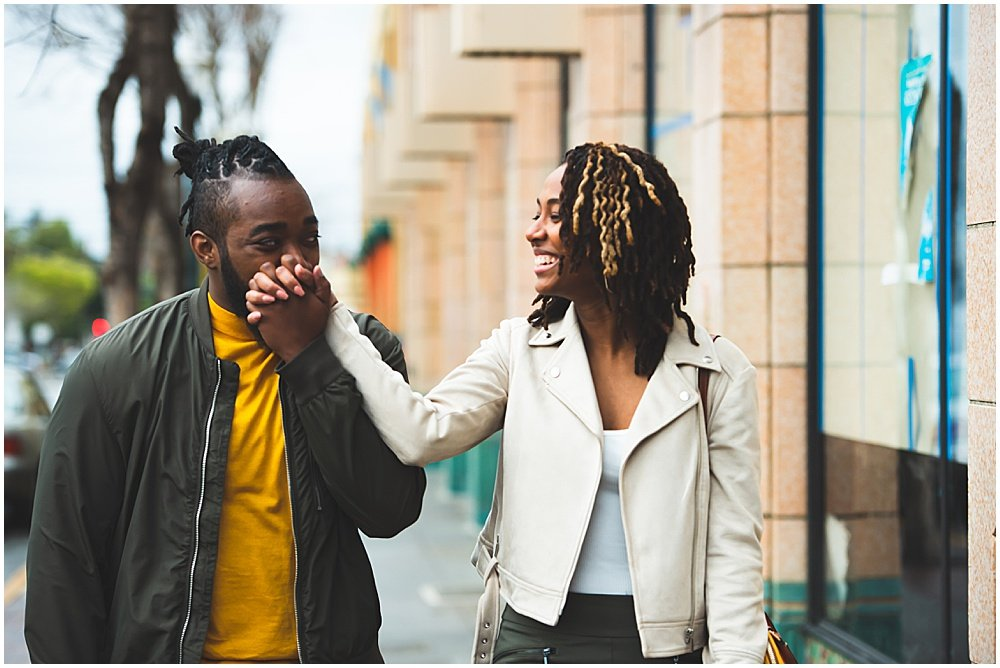 Luther kisses bria's hand for engagement shoot outside restaurant by chloe jackman photography