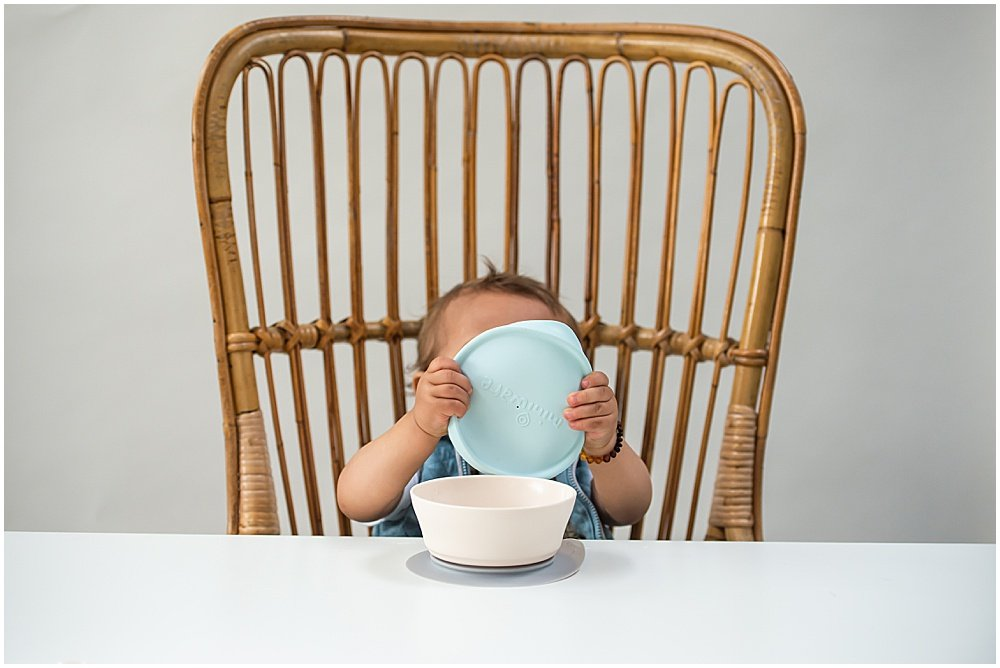 Child with bowl sitting at a table