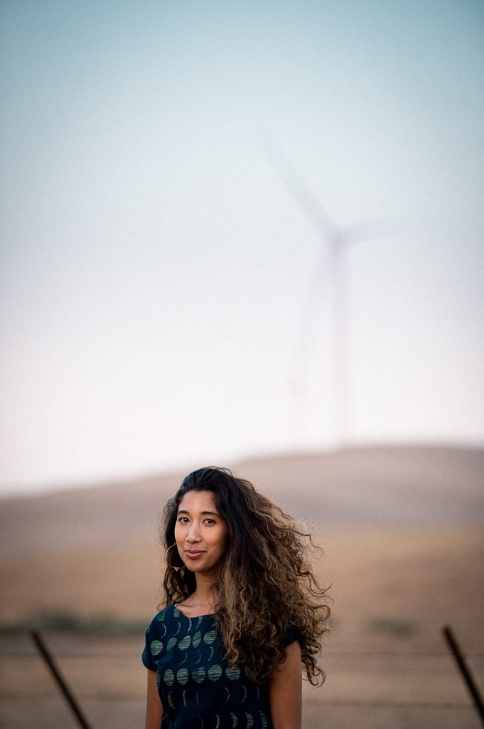 Woman stands in front of windmill