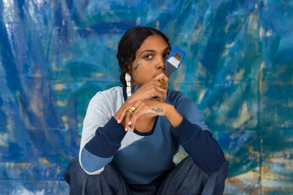 Woman with paint brush covered in blue paint squats in front of painted blue canvas wearing clothes from tonle and GreyJays, two Reclaim Collaborative brands.