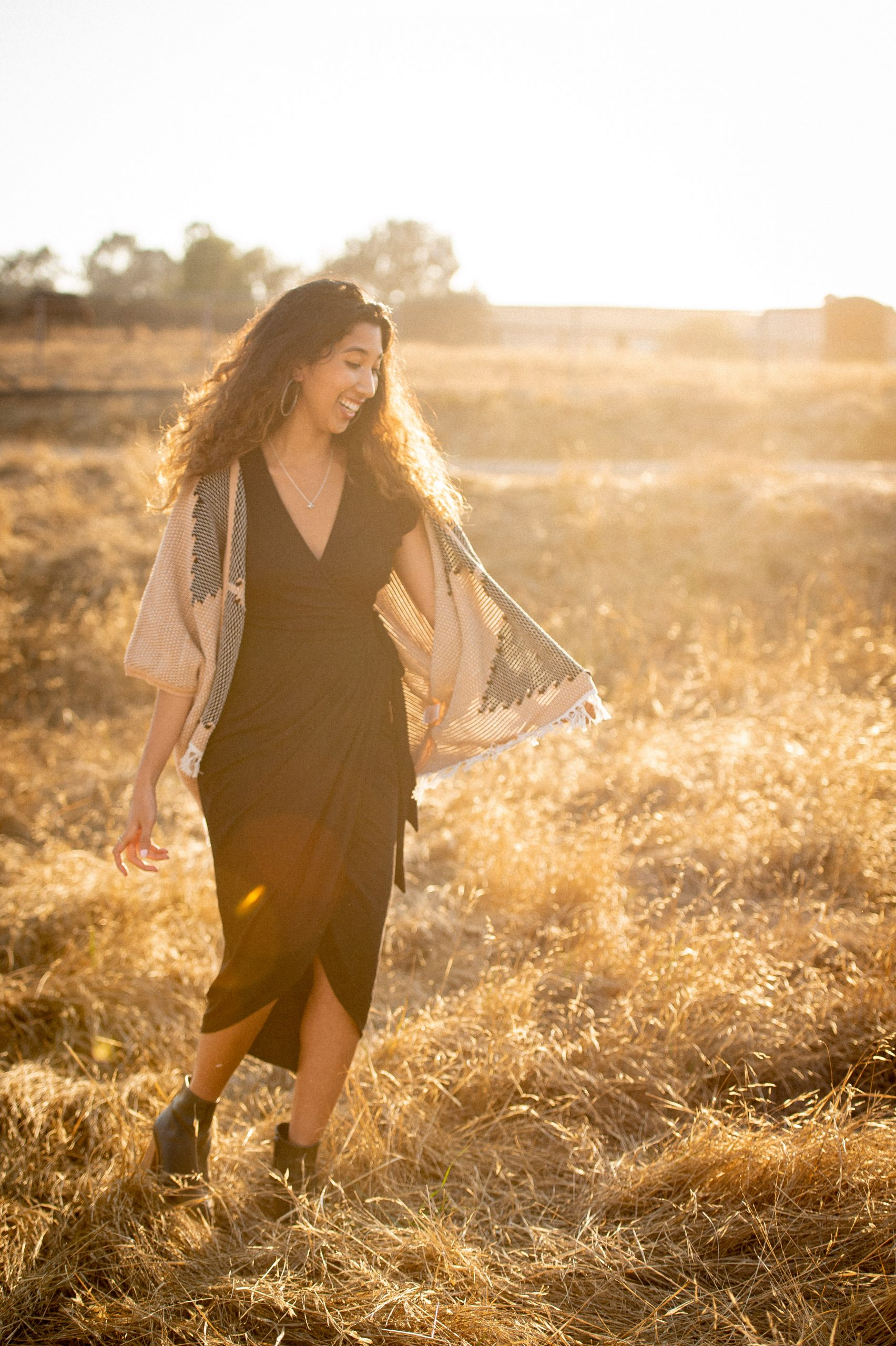 Woman stands in field in shawl from tonle, a Reclaim Collaborative brand.