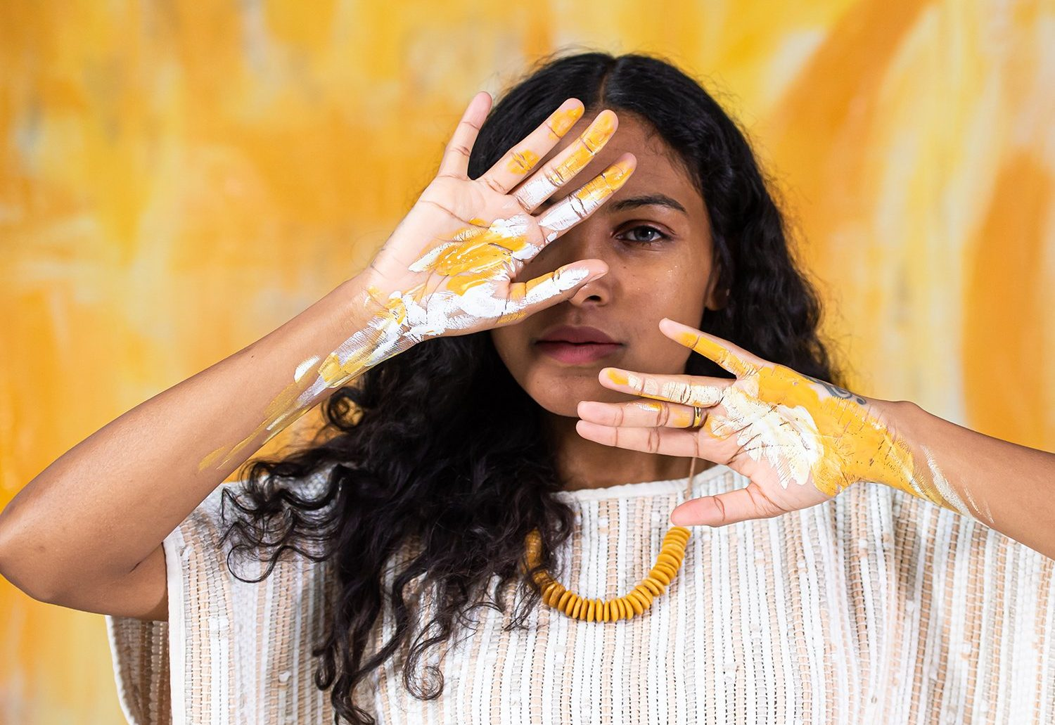Reclaim Collaborative: Woman with yellow paint on her hands holds up hands in front of face. Standing in front of yellow background.